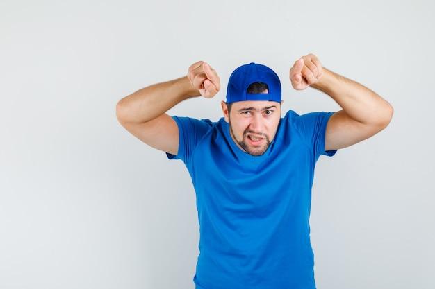 Junger mann im blauen t-shirt und in der kappe, die nach vorne zeigen und sicher schauen