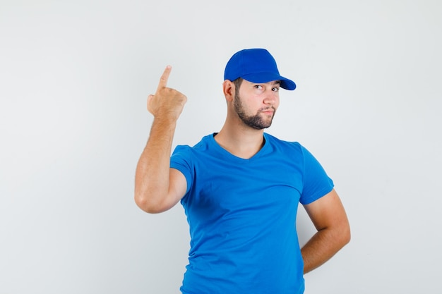 Junger mann im blauen t-shirt und in der kappe, die oben mit der hand auf rücken zeigen und schlau schauen