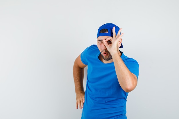Junger mann im blauen t-shirt und in der kappe, die ok zeichen auf auge zeigt und snoopy schaut