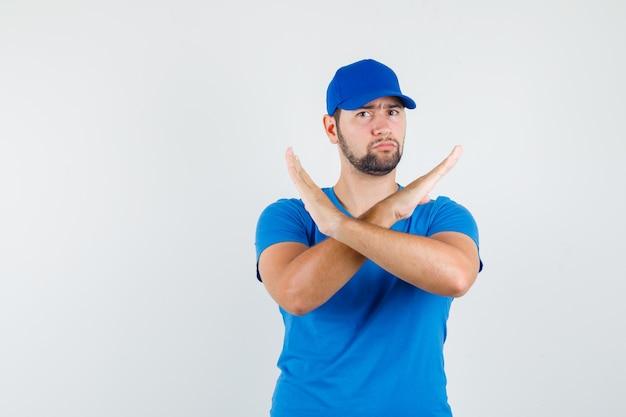 Junger mann im blauen t-shirt und in der kappe, die stoppgeste zeigen und erschöpft schauen