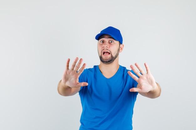 Junger mann im blauen t-shirt und in der kappe, die stoppgeste zeigen