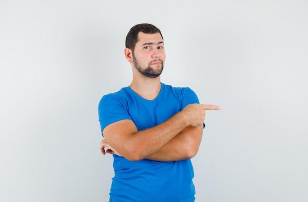 Junger mann im blauen t-shirt zeigt zur seite und sieht selbstbewusst aus