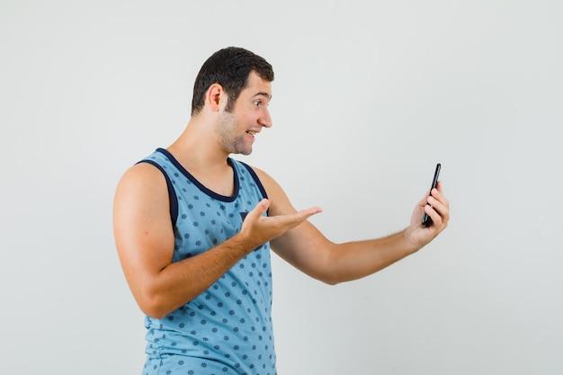 Junger mann im blauen unterhemd, das frage auf video-chat stellt und fröhlich schaut