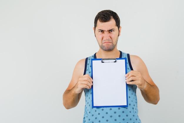 Junger mann im blauen unterhemd hält zwischenablage beim finsteren blick