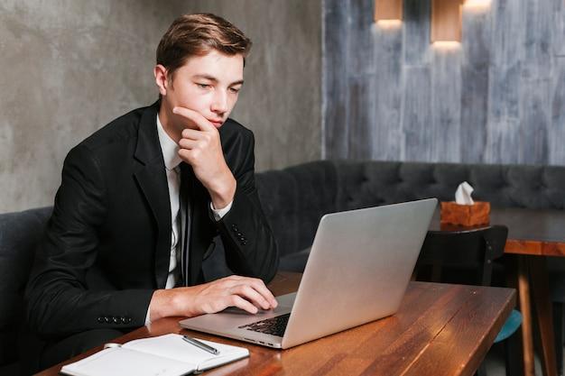 Junger mann im büro, das an dem laptop arbeitet