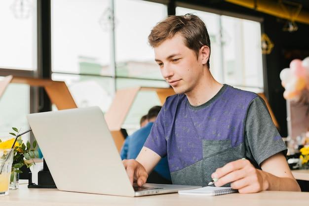 Junger mann im café, das an laptop arbeitet