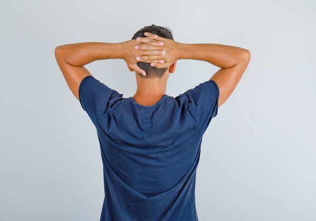 Junger mann im dunkelblauen t-shirt kreuzt hände hinter kopf und schaut entspannt, rückansicht.