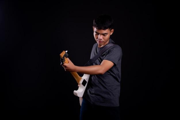 Junger mann im dunklen t-shirt mit e-gitarre