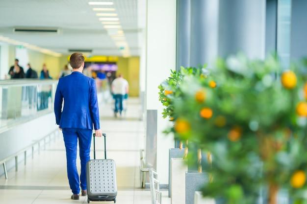 Junger mann im flughafen. tragende anzugsjacke des zufälligen jungen.