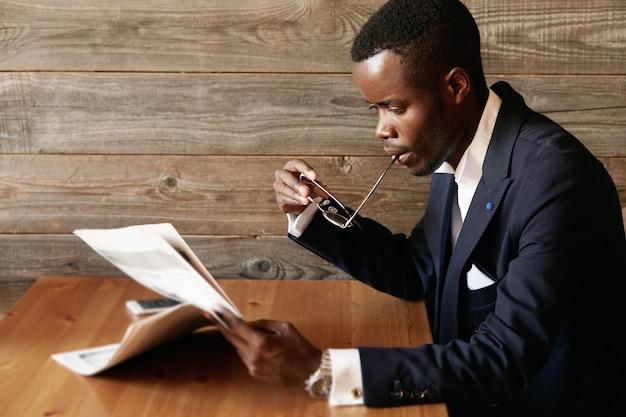 Junger mann im formellen anzug, der im café sitzt