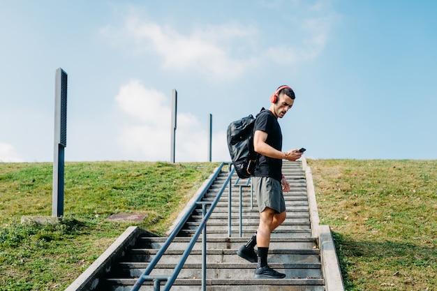 Junger mann im freien unter verwendung des intelligenten telefonhandgriffs