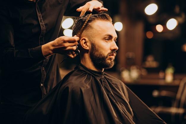 Junger mann im friseursalon, der haare schneidet