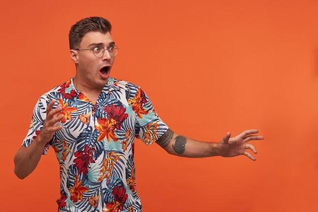 Junger mann im geblümten hemd mit weit geöffnetem mund, der über dem orangefarbenen hintergrund steht, hände hebt, wegschaut, brille trägt, sieht ängstlich aus