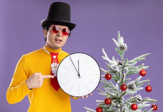 Junger mann im gelben rollkragenpullover und in den gläsern, die schwarzen hut halten, der wanduhr hält, die mit zeigefinger darauf zeigt, mit ernstem gesicht, das neben einem weihnachtsbaum über lila wand steht