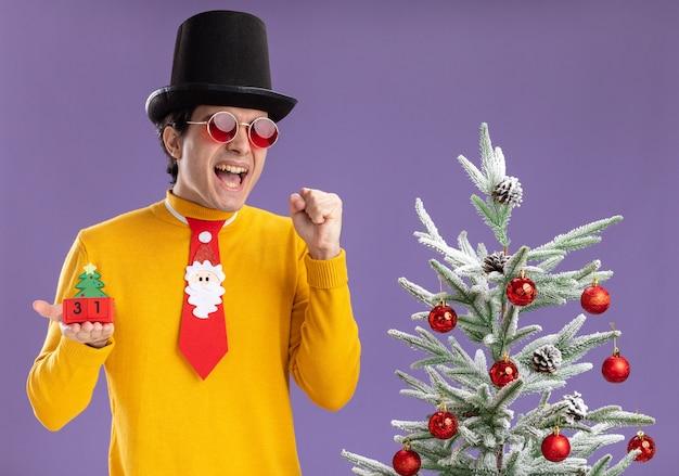 Junger mann im gelben rollkragenpullover und in den gläsern, die schwarzen hut und lustige krawatte halten würfel mit neujahrsdatum aufgeregt und glücklich stehen neben einem weihnachtsbaum über lila hintergrund tragen