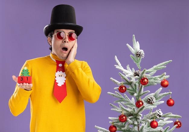 Junger mann im gelben rollkragenpullover und in den gläsern, die schwarzen hut und lustige krawatten halten, die würfel mit neujahrsdatum halten betrachten kamera betrachten, die neben einem weihnachtsbaum über lila hintergrund steht