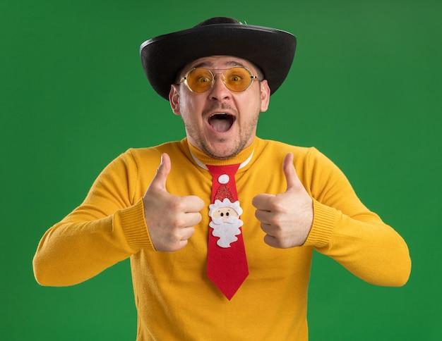 Junger mann im gelben rollkragenpullover und in den gläsern mit lustiger roter krawatte, die daumen oben glücklich und aufgeregt über grüner wand stehend zeigt