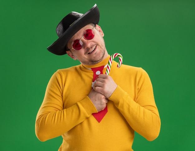 Junger mann im gelben rollkragenpullover und in den gläsern mit lustiger roter krawatte im schwarzen hut, der zuckerstange mit glücklichem gesicht hält, das über grüner wand lächelt
