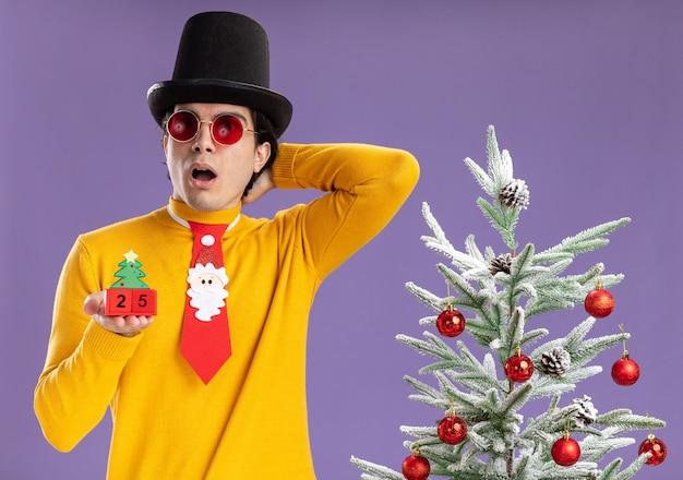 Junger mann im gelben rollkragenpullover und in der brille, die schwarzen hut und lustige krawatte hält, die würfel mit nummer fünfundzwanzig zeigt datum