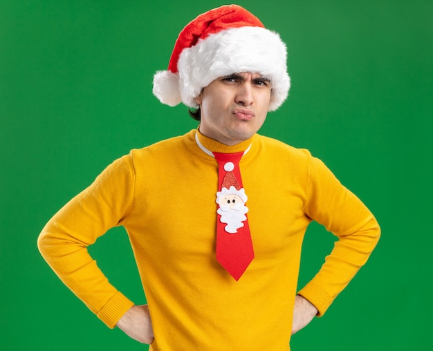 Junger mann im gelben rollkragenpullover und in der weihnachtsmannmütze mit lustiger krawatte, die kamera betrachtet, missfiel mit wütendem gesicht mit händen an der hüfte, die über grünem hintergrund stehen