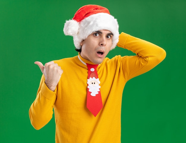 Junger mann im gelben rollkragenpullover und in der weihnachtsmannmütze mit lustiger krawatte, die kamera erstaunt und überrascht betrachtet, zeigt zurück über grünem hintergrund