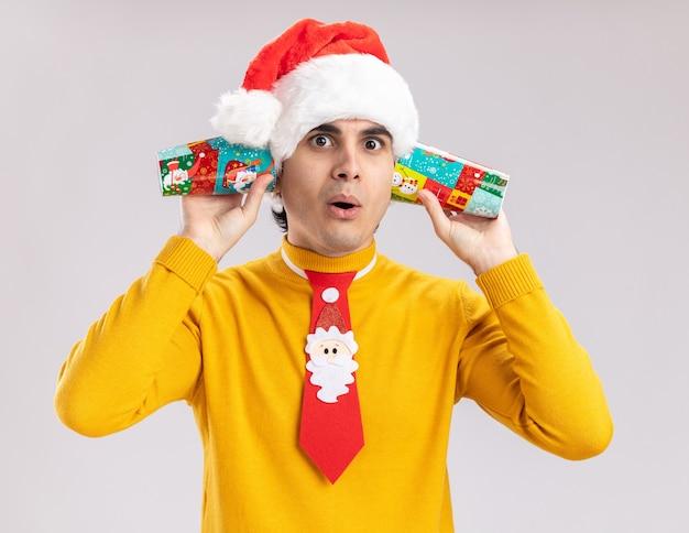 Junger mann im gelben rollkragenpullover und in der weihnachtsmannmütze mit lustiger krawatte, die pappbecher über seinen ohren hält und verwirrt über weißer wand steht