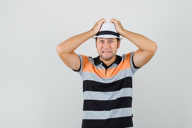 Junger mann im gestreiften t-shirt, hut, der hände auf seinem kopf hält und besorgt aussieht