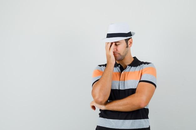 Junger mann im gestreiften t-shirt, hut, der hand auf seinem gesicht hält und müde aussieht