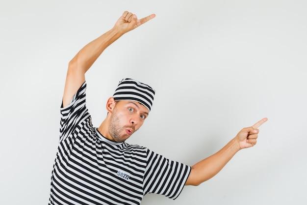 Junger mann im gestreiften t-shirt hut, der weg zeigt und munter aussieht