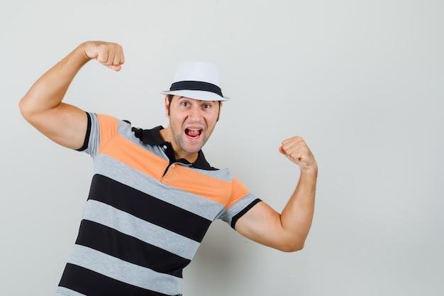 Junger mann im gestreiften t-shirt, hut hebt die hände, während er seine kraft zeigt und energisch aussieht