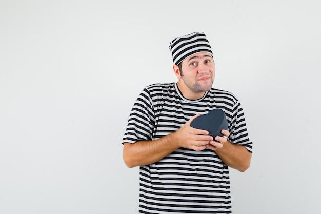 Junger mann im gestreiften t-shirt, kappe, die mini-geschenkbox hält und froh schaut, vorderansicht. platz für text