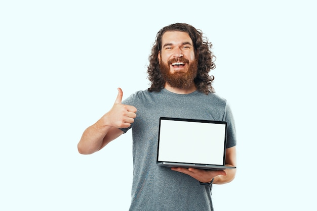 Junger mann im grauen hemd, der laptop mit weißem bildschirm hält und daumen nach oben zeigt und lächelt