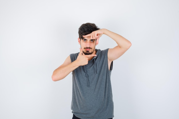 Junger mann im grauen hemd mit rahmengeste und ernstem blick