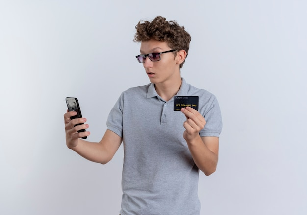 Junger mann im grauen poloshirt, das seinen smartphone-bildschirm betrachtet, der verwirrte kreditkarte zeigt, die über weißer wand steht
