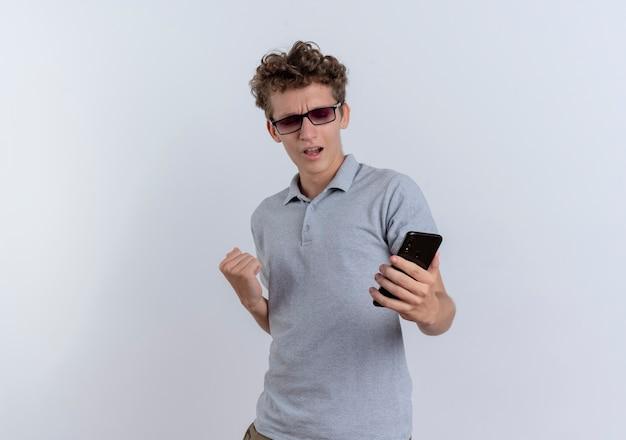 Junger mann im grauen poloshirt, der seinen smartphonebildschirm betrachtet, der die faust ballt, die seinen erfolg erfreut, der über weißer wand steht