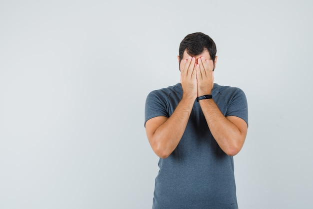 Junger mann im grauen t-shirt, das hände auf gesicht hält und deprimiert aussieht