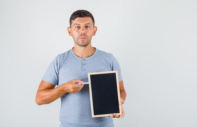Junger mann im grauen t-shirt, das kreide auf tafel zeigt