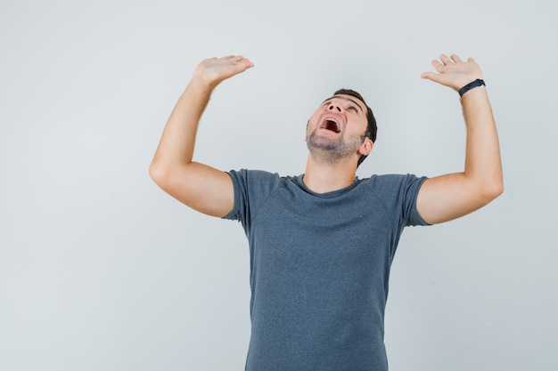Junger mann im grauen t-shirt, das vorbeugend palmen hebt und erschrocken aussieht