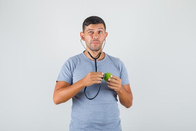 Junger mann im grauen t-shirt, der grünen apfel mit stethoskop untersucht und vorsichtig schaut