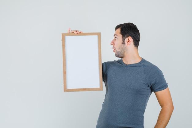 Junger mann im grauen t-shirt, der leeren rahmen hält und konzentriert schaut