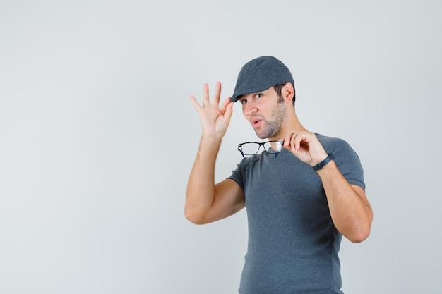 Junger mann im grauen t-shirt hält brille, die seine kappe justiert und stolz schaut