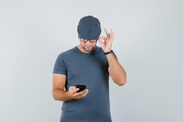 Junger mann im grauen t-shirt, kappe, die handy benutzt und beschäftigt schaut, vorderansicht.