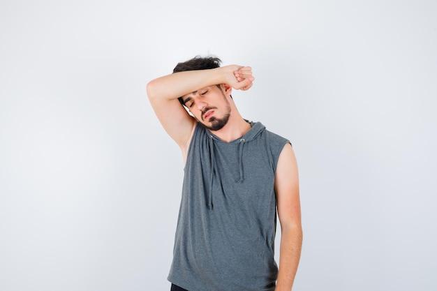 Junger mann im grauen t-shirt legt den arm auf die stirn und sieht ernst aus