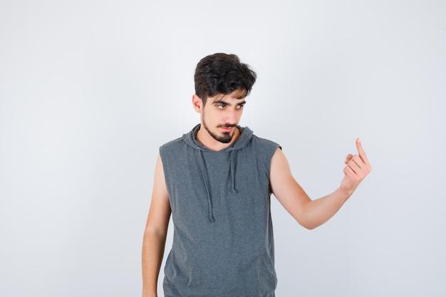 Junger mann im grauen t-shirt zeigt nach oben und sieht ernst aus