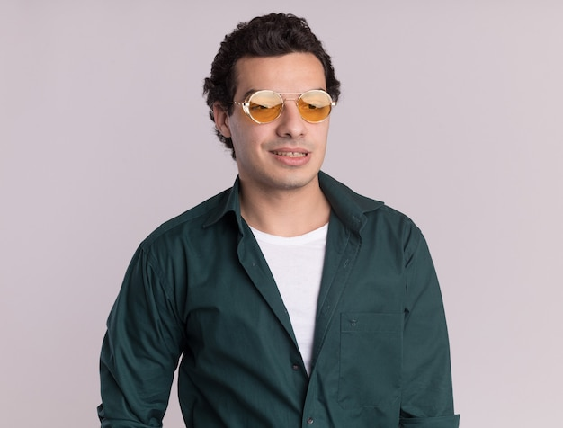 Junger mann im grünen hemd, das brillen trägt, die beiseite mit lächeln auf gesicht stehen, das über weißer wand steht