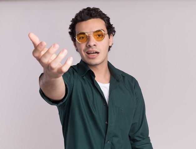 Junger mann im grünen hemd, das die brille trägt, die vorne mit arm heraus fragt, der über weißer wand steht