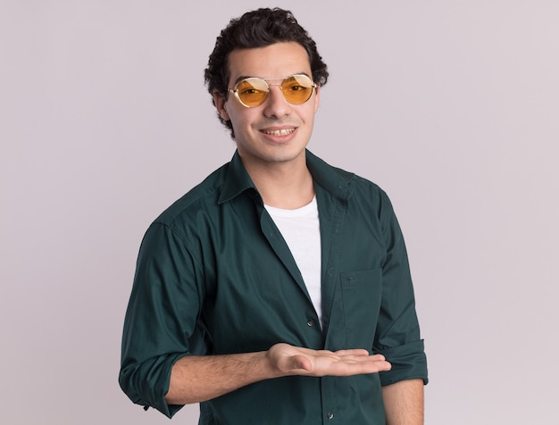 Junger mann im grünen hemd, das die brille trägt, die vorne mit dem lächeln auf gesicht schaut, das etwas mit dem arm der hand darstellt, der über weißer wand steht
