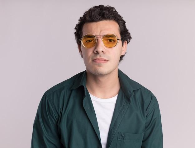 Junger mann im grünen hemd, das die brille trägt, die vorne mit traurigem ausdruck über weißer wand steht