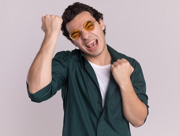 Junger mann im grünen hemd, das die glücklichen und aufgeregten geballten fäuste der brille trägt, die über weißer wand stehen