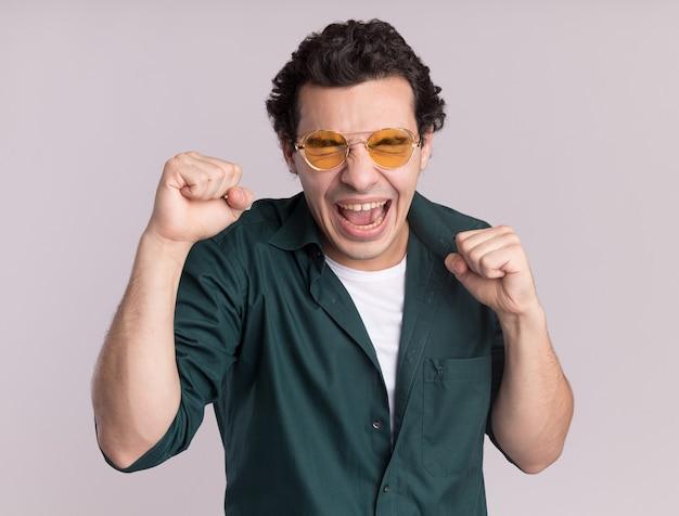 Junger mann im grünen hemd, das die glücklichen und aufgeregten geballten fäuste der brille trägt und sich über seinen erfolg freut, der über weißer wand steht